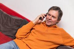 Adulto mayor en un sofá con el teléfono Fotografía de archivo libre de regalías