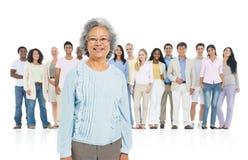 Adulto mayor que se coloca hacia fuera de la muchedumbre Imagen de archivo libre de regalías