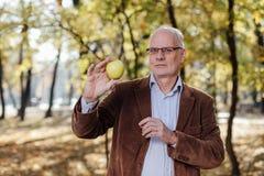 Adulto mayor que sostiene la manzana verde Imagenes de archivo