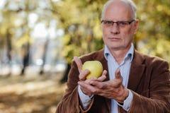 Adulto mayor que sostiene la manzana verde Fotografía de archivo libre de regalías