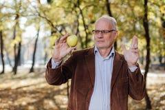 Adulto mayor que sostiene la manzana verde Foto de archivo libre de regalías