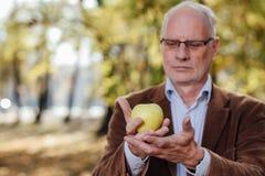 Adulto mayor que sostiene la manzana verde Fotos de archivo libres de regalías