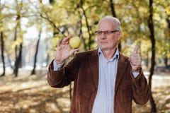 Adulto mayor que sostiene la manzana verde Imágenes de archivo libres de regalías