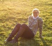 Adulto, mujer agradable que se sienta en prado de la hierba Foto de archivo