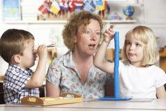 Adulto que ayuda a dos niños jovenes en Montessori/pre Fotos de archivo libres de regalías