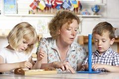 Adulto que ayuda a dos niños jovenes en Montessori/pre Imagenes de archivo