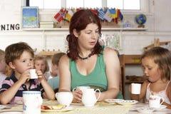 Adulto que juega con dos niños en Montessori/Pre- Imagen de archivo