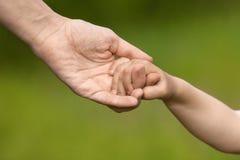 Adulto que lleva a cabo una mano del niño Imagen de archivo libre de regalías