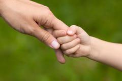 Adulto que lleva a cabo una mano del niño en fondo borroso Imagen de archivo libre de regalías