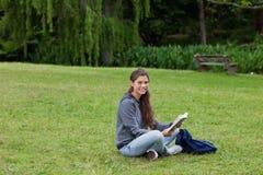 Adulto que sostiene un libro mientras que se sienta a piernas cruzadas Imagen de archivo