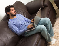 Adulto que trabaja en casa El sentarse en sofá marrón en la sala de estar Imagen de archivo