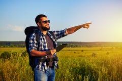 Adulto sano en gafas de sol con la mochila que lleva a cabo una tableta y un p Imágenes de archivo libres de regalías