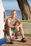 Adulto sonriente que se sienta con la tabla hawaiana Imágenes de archivo libres de regalías