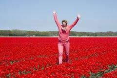 Adulto womanjumping en campo rojo del tulipán Foto de archivo libre de regalías