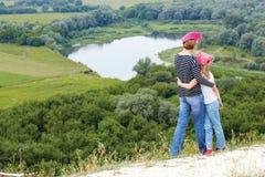 Adulto y niño que se colocan en una cima de la montaña cerca del río Fotos de archivo libres de regalías