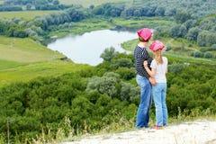 Adulto y niño que se colocan en una cima de la montaña cerca del río Imagenes de archivo