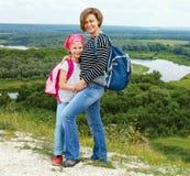 Adulto y niño que se colocan en una cima de la montaña cerca del río Foto de archivo libre de regalías