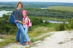 Adulto y niño que se colocan en una cima de la montaña cerca del río Foto de archivo
