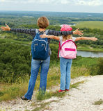 Adulto y niño que se colocan en una cima de la montaña cerca del río Fotografía de archivo