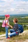 Adulto y niño que se colocan en una cima de la montaña cerca del río Madre w Imagenes de archivo