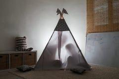 Adulto y niño que se sientan en una tienda de los indios norteamericanos en el cuarto de niños Fotos de archivo libres de regalías