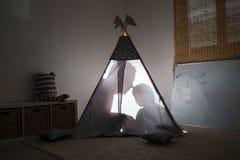 Adulto y niño que se sientan en una tienda de los indios norteamericanos en el cuarto de niños Imagen de archivo