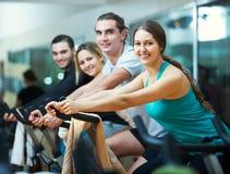 Adultos activos que montan las bicicletas inmóviles Fotos de archivo