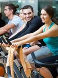 Adultos activos que montan las bicicletas inmóviles Imagen de archivo