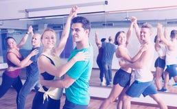 Adultos alegres que bailan bachata junto Foto de archivo