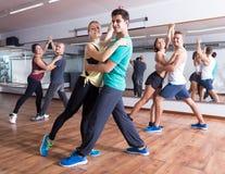 Adultos amistosos que bailan bachata junto Imagen de archivo libre de regalías