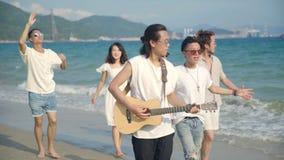 Adultos asiáticos jovenes que caminan el canto en la playa almacen de video