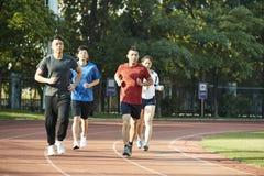 Adultos asiáticos jovenes que corren en pista Fotografía de archivo