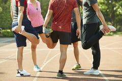 Adultos asiáticos jovenes que estiran las piernas en pista Foto de archivo libre de regalías