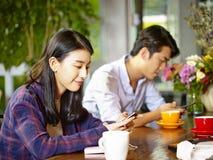 Adultos asiáticos jovenes que juegan con el teléfono móvil en cafetería Imagen de archivo libre de regalías