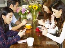 Adultos asiáticos jovenes que juegan con el teléfono móvil en cafetería Fotografía de archivo libre de regalías