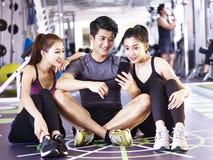 Adultos asiáticos jovenes que miran el teléfono móvil en gimnasio Imágenes de archivo libres de regalías