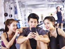 Adultos asiáticos jovenes que miran el teléfono móvil en gimnasio Fotografía de archivo