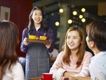 Adultos asiáticos jovenes que se relajan en cafetería Foto de archivo