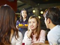 Adultos asiáticos jovenes que se relajan en cafetería Fotos de archivo