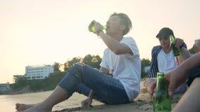 Adultos asiáticos jovenes que sientan la relajación en la cerveza de consumición de la playa almacen de metraje de vídeo