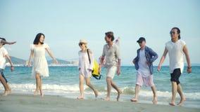 Adultos asiáticos novos que têm o divertimento que anda na praia video estoque