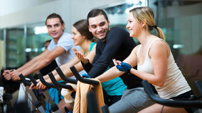 Adultos ativos que montam bicicletas estacionárias Foto de Stock