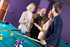 Adultos con el vino en la tabla de billar Foto de archivo libre de regalías