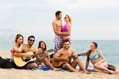 Adultos con la guitarra en la playa Imagenes de archivo