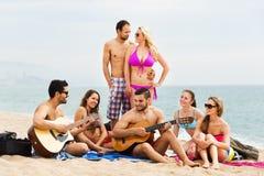 Adultos con la guitarra en la playa Imagen de archivo libre de regalías