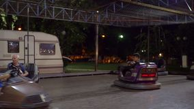 Adultos con los niños que se divierten que conduce los coches de parachoques en la feria de diversión almacen de metraje de vídeo