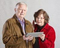 Adultos confusos con la tableta Imagen de archivo libre de regalías