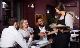Adultos de charla y camarera alegre Foto de archivo libre de regalías