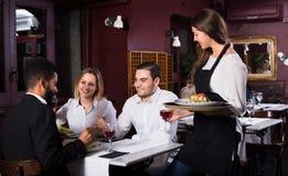 Adultos de charla y camarera alegre Imagen de archivo libre de regalías