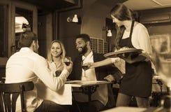 Adultos de charla y camarera alegre Imagen de archivo